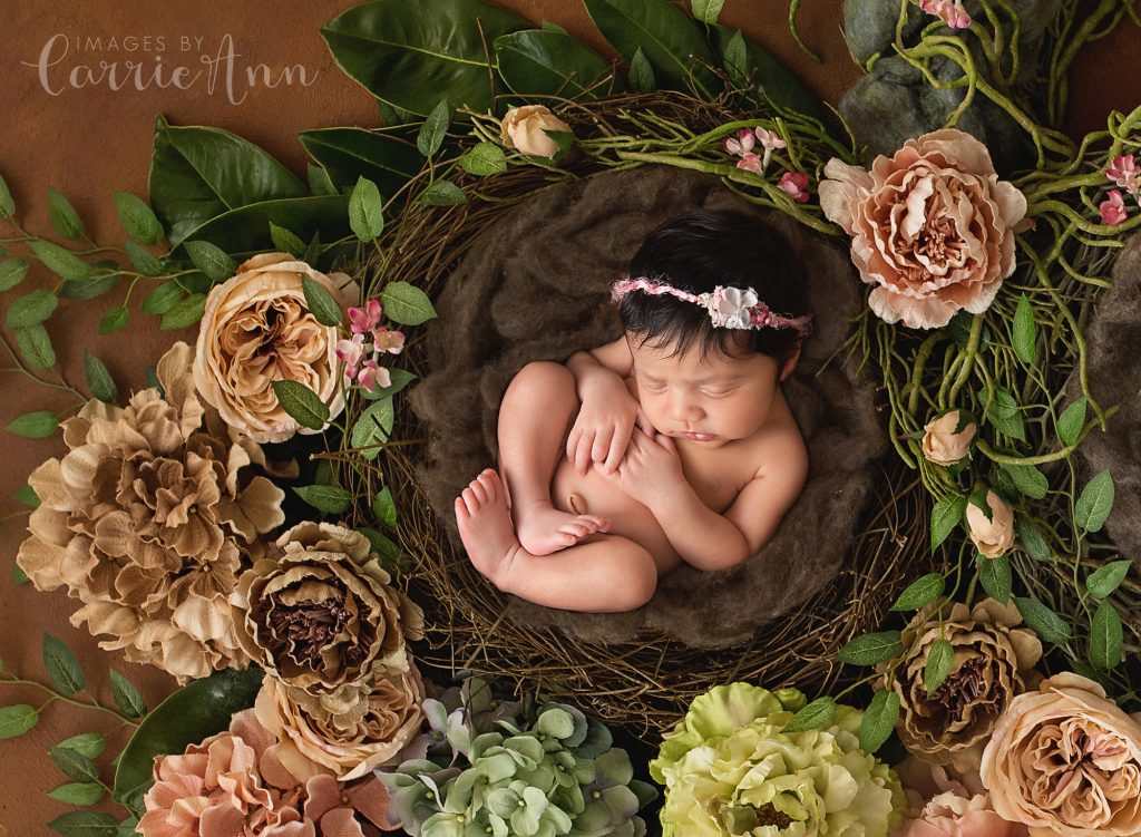 baby girl in nest with flowers