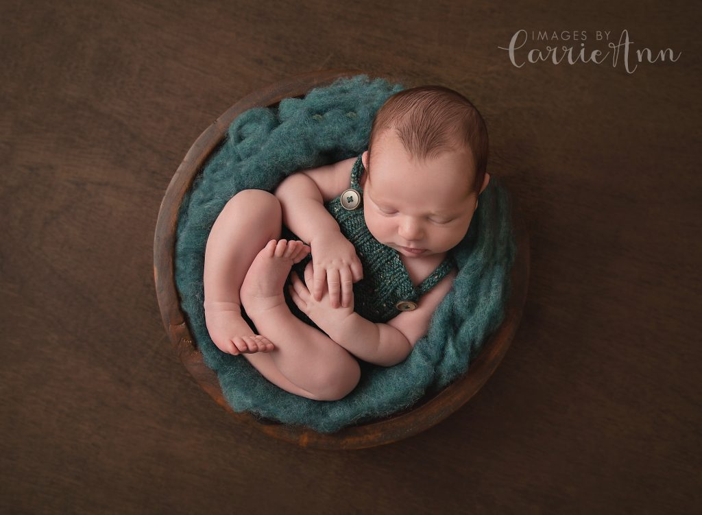 newborn boy in green outfit in bowl taken by Images by Carrie Ann