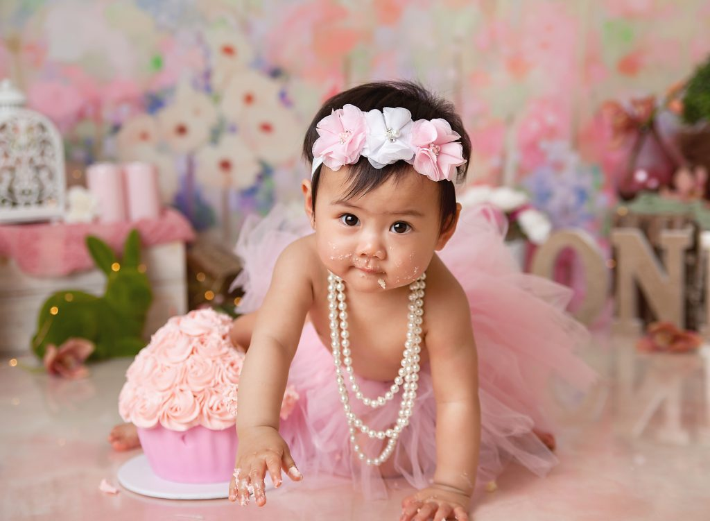 one year old in tutu sitting next to Giant cupcake