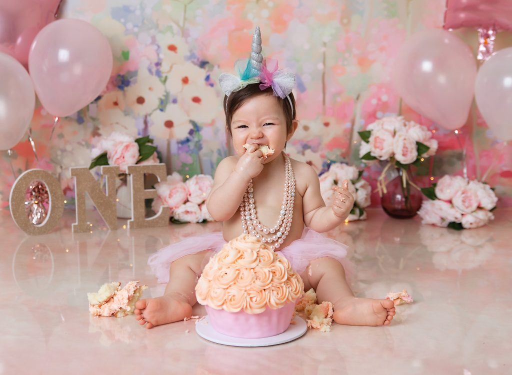 one year old girl eating cake for her birthday cake smash session