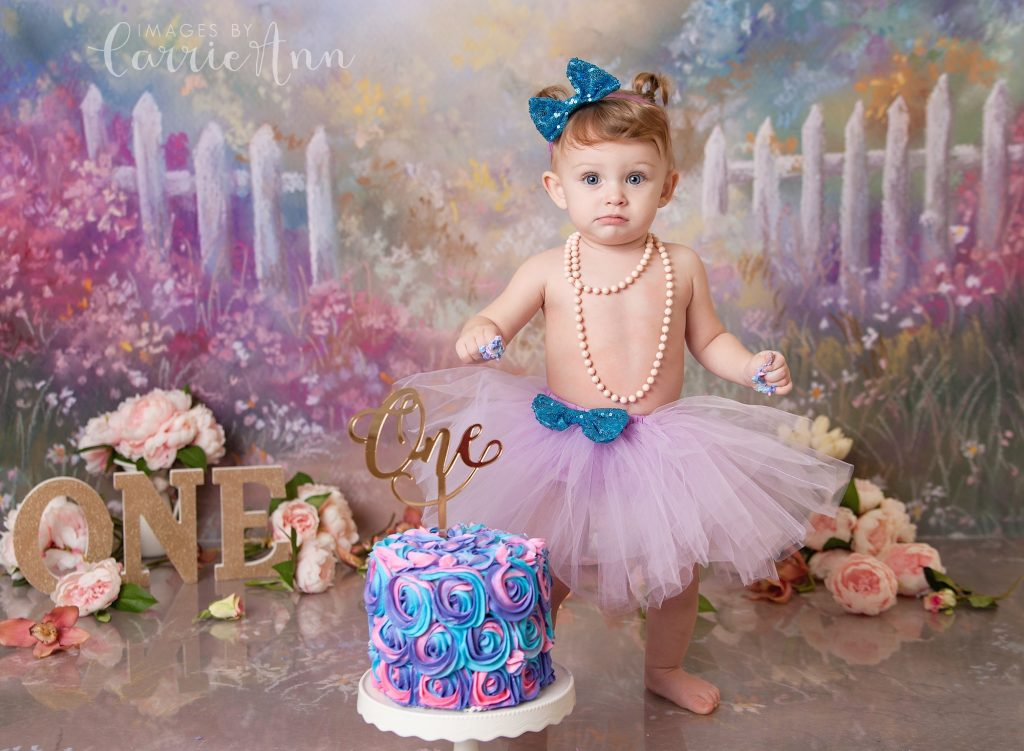 one year old girl eating cake for birthday
