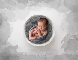 Newborn baby boy in grey wrap