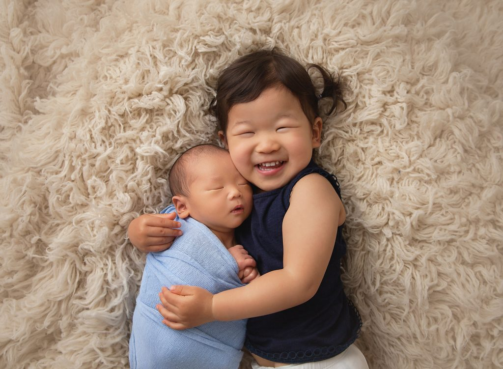 Big sister cuddling newborn brother and laughing