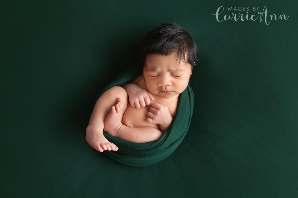 baby girl with dark hair on green blanket and wrap