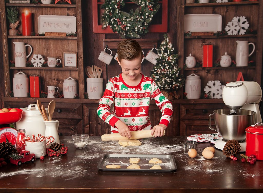 boy rolling dough for cookie in christmas kitchen