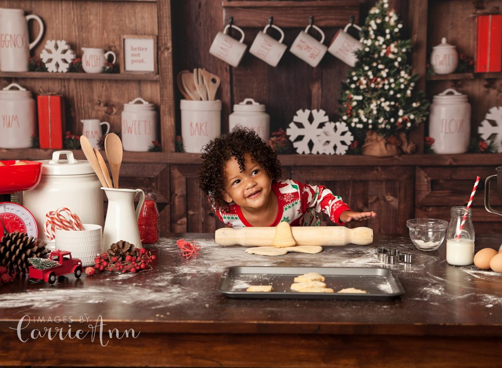 Girl playing in kitchen with rolling pin making christmas cookies